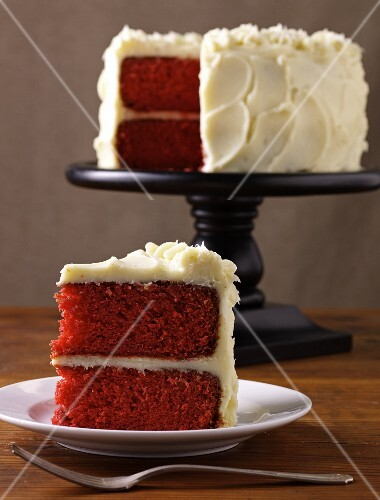 Slice of Red Velvet Cake on a Plate with Whole Cake on Cake Dish