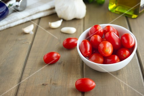Grape Tomatoes and Garlic Cloves on a Wooden Table