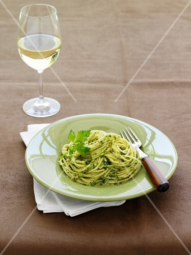 Spaghetti with parsley pesto, white wine glass