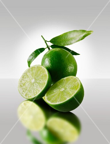 Two lime halves in front of a whole lime