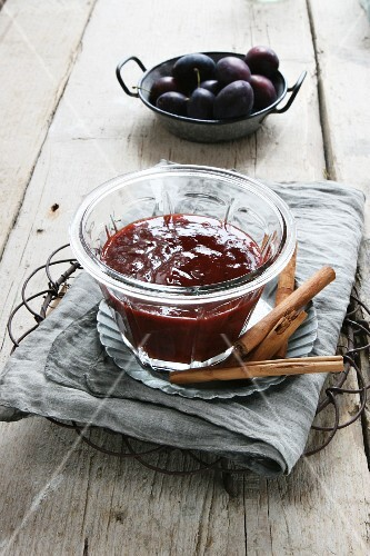 Homemade plum compote with cinnamon sticks
