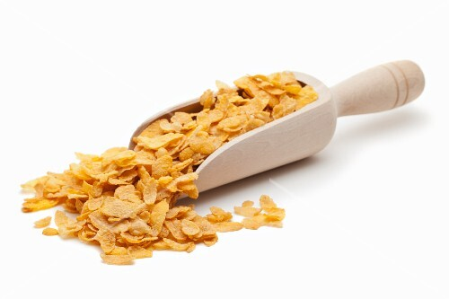 Cornflakes on wooden scoop against a white background