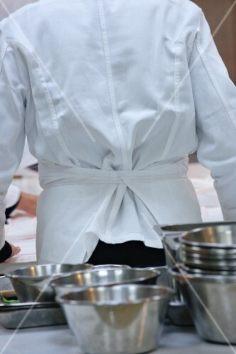 A chef and stainless steel bowls in a commercial kitchen