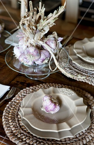 A garlic clove on a place setting on the table in a country house kitchen (Provence, France)