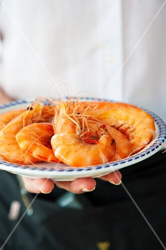 A waitress serving a plate of king prawns