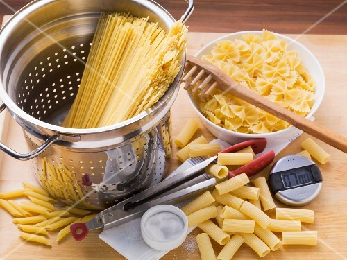 Various types of pasta, a colander, a spaghetti server, tongs and a kitchen timer