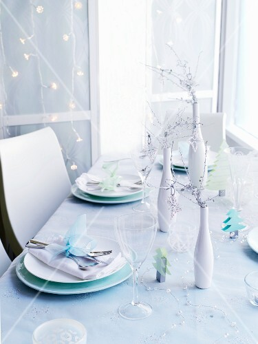 A table laid for Christmas in front of a wall hung with a chain of lights