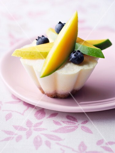 A mini cheesecake topped with fruits