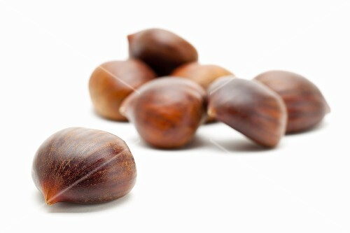 Edible chestnuts on a white surface
