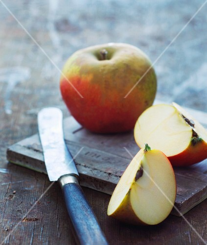 Apple wedges and a whole apple with a knife on a chopping board