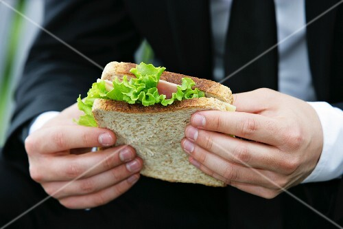A man holding a ham and cheese sandwich