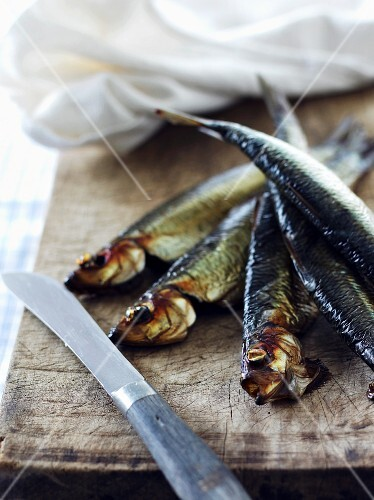 Smoked herring on a wooden board with a knife