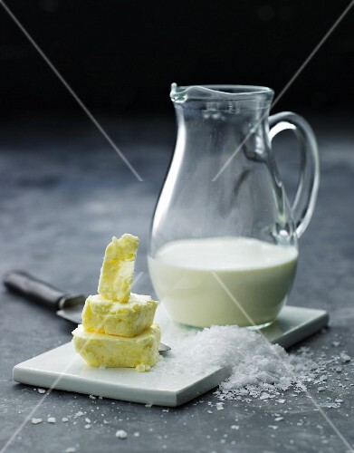 An arrangement of butter pieces, coarse salt and a jug of milk