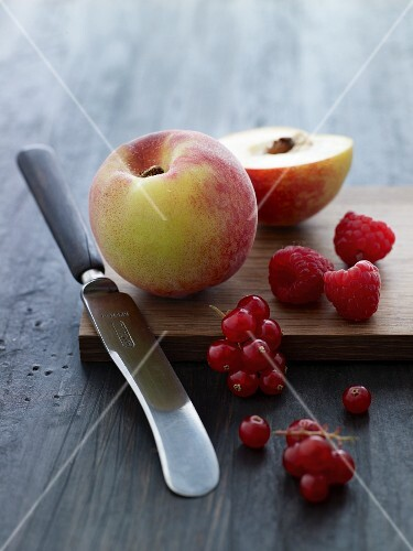 Peaches, redcurrants and raspberries on a wooden board with a knife