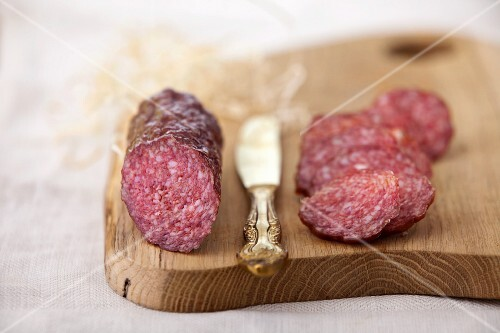 Salami, partially sliced, on a chopping board