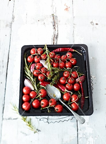 Cherry tomatoes with herbs and chilli pepper on a baking tray