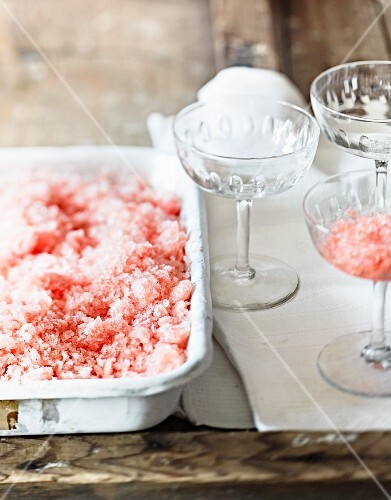 Watermelon granita in an ice cream bowl with empty glasses