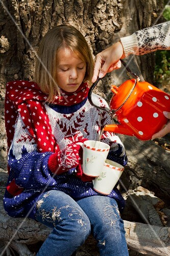 A hot drink being poured into a mug held by little girl