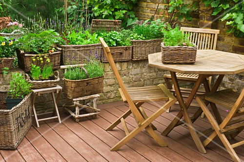 Table, chairs and wicker planters of herbs and lettuce on terrace