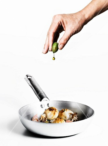 A hand squeezing olive oil from an olive onto sepia with garlic