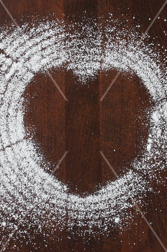 Icing sugar on a wooden surface creating a heart shape