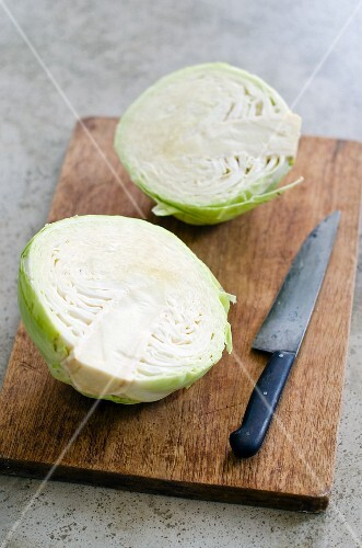 White cabbage, halved, on chopping board