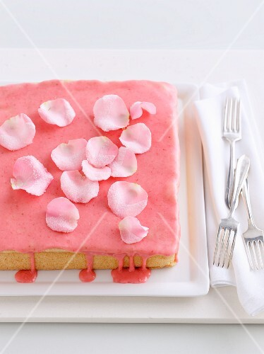 Sponge cake with strawberry icing and rose petals