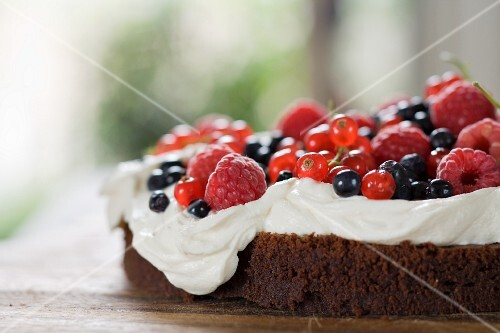 Chocolate cake topped with cream and berries