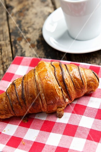 A chocolate croissant on a checked cloth