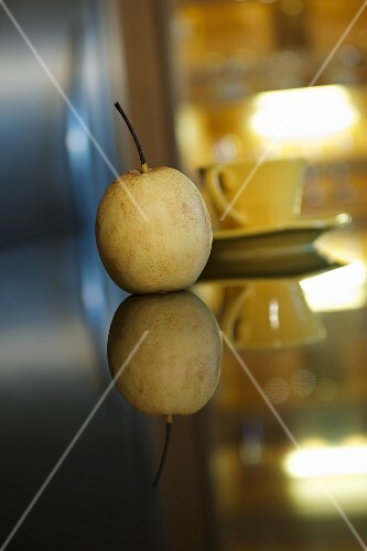 A nashi pear on a mirrored table