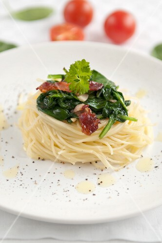 Noodle nest with spinach, dried tomatoes, bacon and parsley