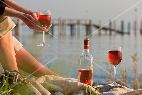 A woman on the bank of a lake with rose wine