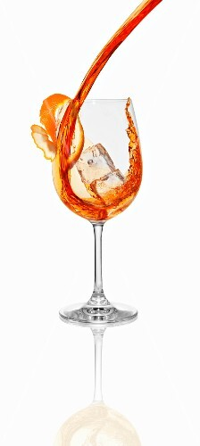 Aperol being poured into a glass with an ice cube