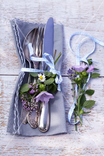 Napkin with cutlery and posies of fresh herbs