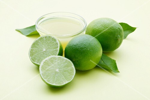 A bowl of lime juice and fresh limes