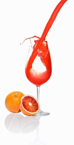 Blood orange juice being poured into a glass
