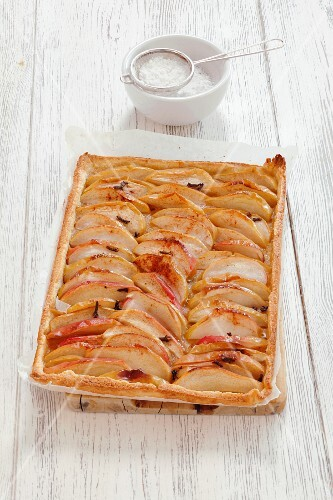 A whole apple and cinnamon tart with icing sugar