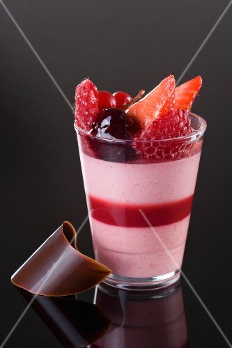 A layered dessert with fruit mousse and berries