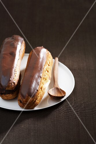 Two chocolate eclairs on a plate with a wooden spoon