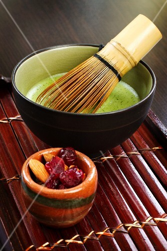 Matcha tea with a tea whisk and almonds and dried cranberries