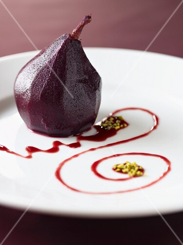 A red wine pear with chopped pistachios