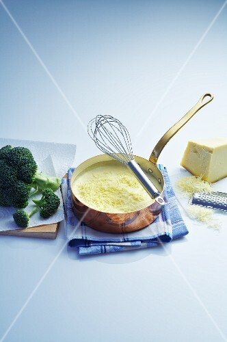 Cheese sauce in a copper pan, broccoli and a piece of cheese