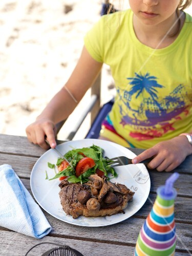 A girl eating a grilled steak with mushrooms