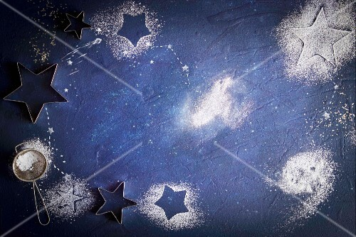 Icing sugar stars on a blue surface
