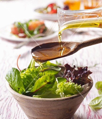 Oil being pored over salad from a wooden spoon