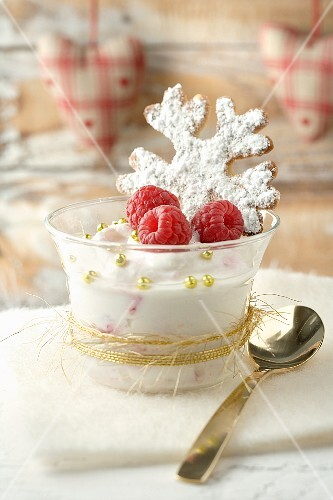 Cream dessert with raspberries and a snowflake biscuit for Christmas