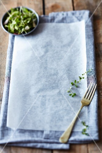 A grey tea towel and baking paper on a rustic wooden table
