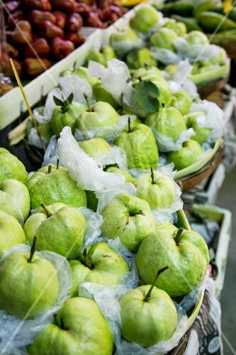 Fresh guavas wrapped in foil at a market in Thailand