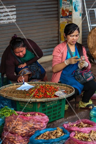 Market women counting money at a market in Vientiane, Laos