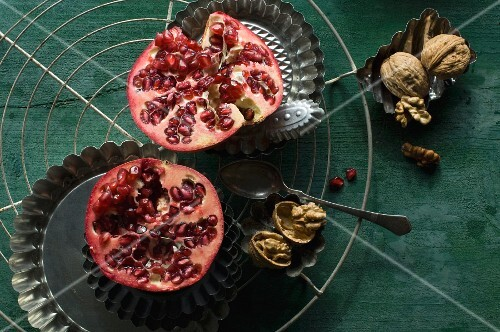 A halved pomegranate with a baking tin and walnuts on a wire rack